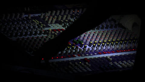 Sound engineer that regulates sound quality mixer revolves buttons at light a to Live Action