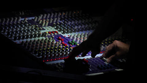 Sound engineer that regulates sound quality mixer revolves buttons at light a to Footage