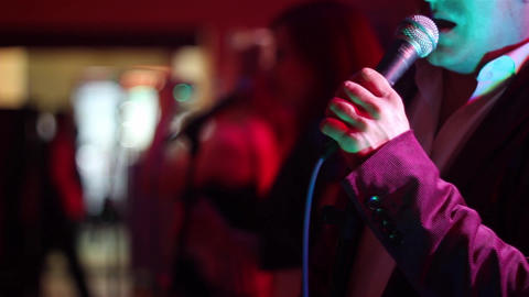 Man singing at the microphone during a concert of light music or a design contes Footage