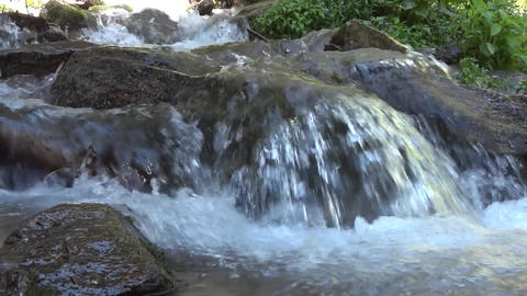 Fast mountain river forming waterfalls as it passes over boulders 05 Footage