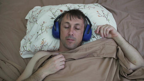 Man Sleeping in Daytime With Earmuffs Footage