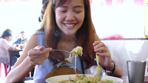 Young beautiful woman eating noodle in local restaurant Footage