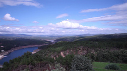 Pan view of river formed by dam surrounded by forest Footage