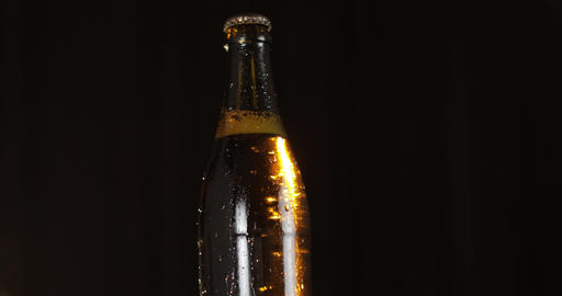 Bottle of cold beer on a black background. It slowly rotates. Condensate Footage