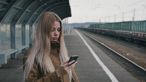 A beautiful girl uses a smartphone at the station Live Action
