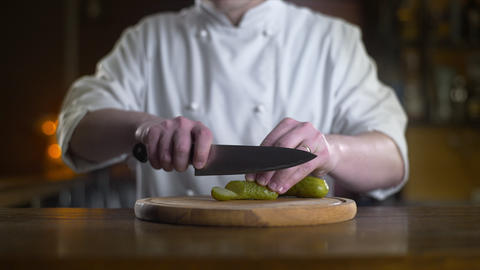 The cook cuts pickle on the wooden board in a bar in slow motion, cooking burger Live Action