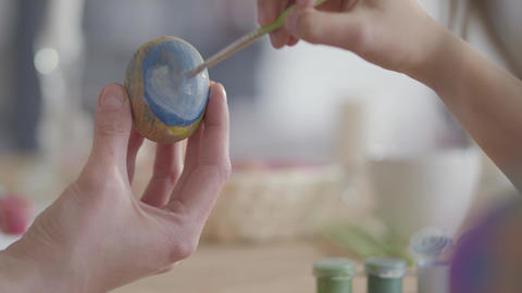 Close up of mother and daughter hands coloring easter eggs with colors and brush Live Action