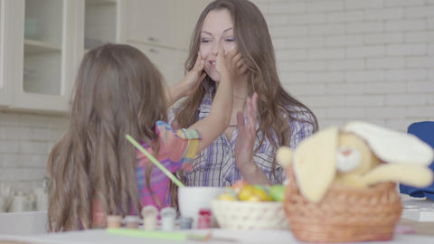 Young mother and cute girl chatting on the kitchen. The kid touches mother's Live Action