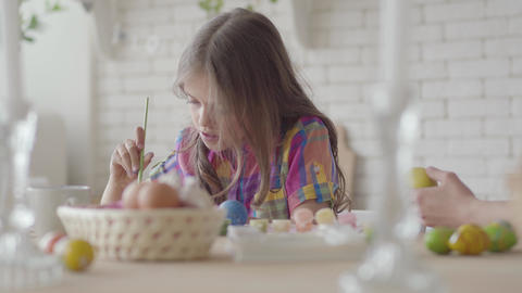 Mom and little girl coloring easter eggs with colors and brush. Preparation for Live Action