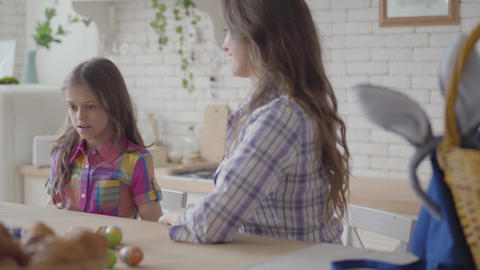 Young mother and cute girl sitting in the kitchen. Little girl takes two Easter Footage