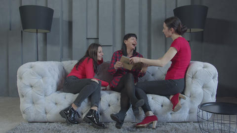 Females watching album sitting on sofa at home Live Action