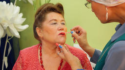 Elderly woman is painting her friend's lips for the party with lip gloss Footage