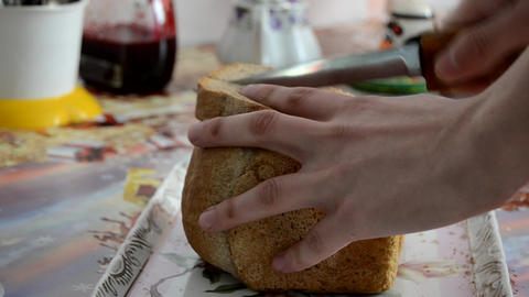 A Man Cutting a Loaf of Bread with a Bread Knife Footage