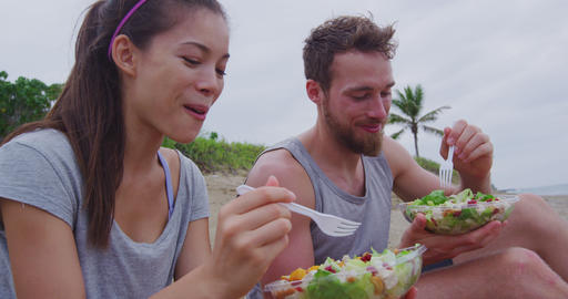 Happy young people eating healthy salad for lunch on beach laughing together Footage