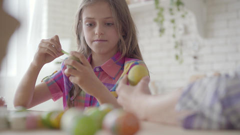Pretty little daughter coloring easter eggs with colors and brush. Preparation Live Action