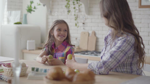 Pretty young woman and cute little daughter coloring easter eggs with colors and Live Action