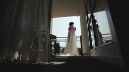 Beautiful bride in a wedding dress. The girl in the morning at the window Archivo