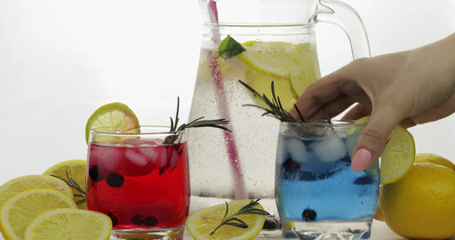 Woman hand takes refreshing soda lemonade red and blue cocktails with lemon Footage