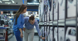 Young married couple man and woman in casual clothes appliances store choose to Footage