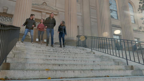 Two young men and two young women walking down library stairs in slow motion Live Action