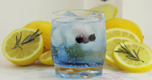 Stir a cold drink in drinking glass. Making refreshing soda blue cocktail Footage