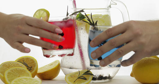 Woman and man hands takes refreshing soda red and blue cocktails with lemon Footage