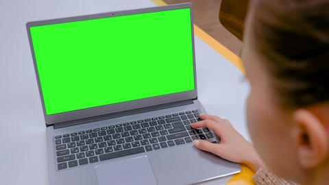 Woman looking at laptop computer with blank green screen in cafe GIF