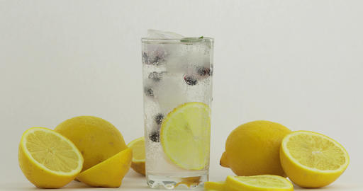 Pour a cold soda drink. Lemon and ice in a drink glass.... Stock Video Footage