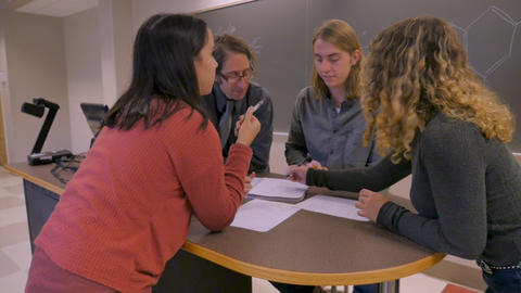 Female student solving problems in a classmates paper notebook in a classroom with a professor to Footage