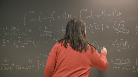 Young female college or university student solving a complex math problem on a blackboard in slow Footage