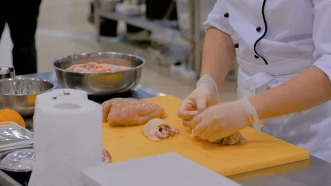 Cook cutting chicken meat with knife GIF