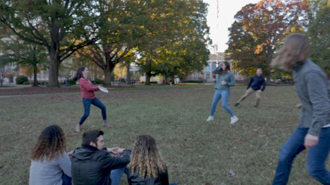 College friends playing frisbee together on a beautiful fall day on a university campus in slow Footage