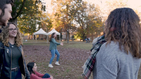 Camera circling around happy smiling friends talking on college campus while a woman is playing Live Action
