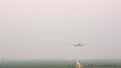 Airplane landing on runway in fog Archivo