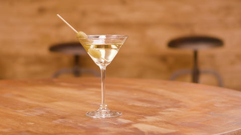 A glass of martini with olives on a wooden table Footage
