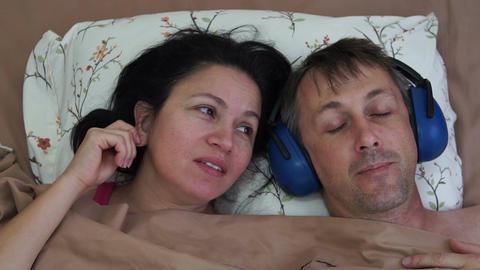 Man Sleeping in Earmuffs and Woman Talking Footage