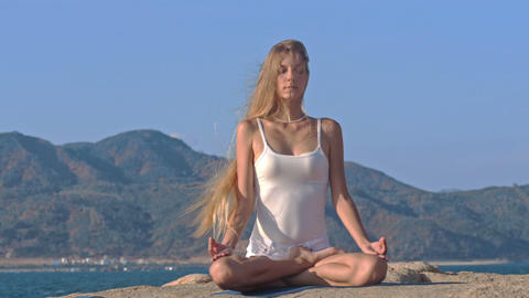 Blond Girl in Top Relaxes in Yoga Pose Lotus on Rock Footage