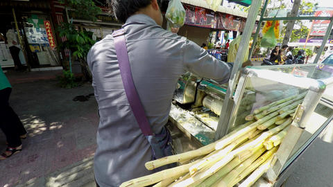 Vendor with a portable sugar cane juicer fresh raw sugar cane drinks Live Action