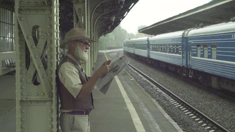 Old Man With Newspaper On Train Station Footage