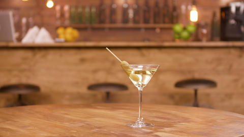 Parallax shot of a martini glass on an empty wooden table with bar counter on Footage