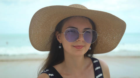 portrait of beautiful young woman with hat and sunglasses on beach Archivo