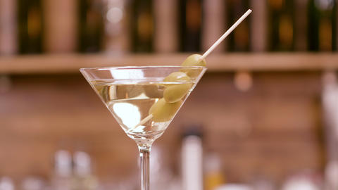 Clean close up parallax shot of a martini glass garnished with olives Footage