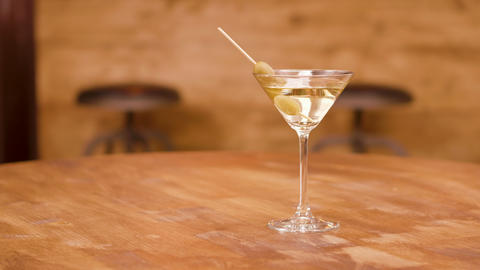 Parallax shot of a martini glass on an empty wooden table Footage