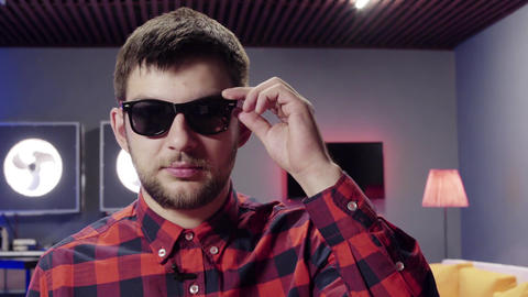 Handsome guy takes off sunglasses and massages his ears in nice furnished room Footage