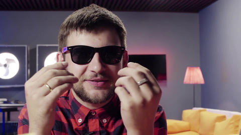 Attractive guy speaks, uses hand gestures looking at camera in furnished room Footage