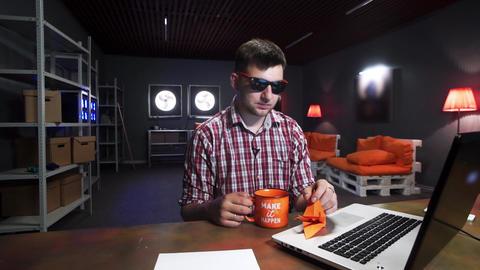 Handsome caucasian guy with sunglasses is folding cute orange origami crane Footage
