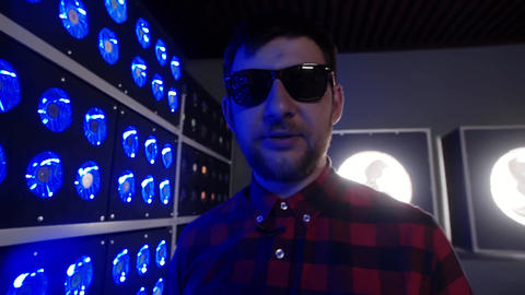 Young man with sunglasses speaks at camera next to blue illuminated coolers Footage