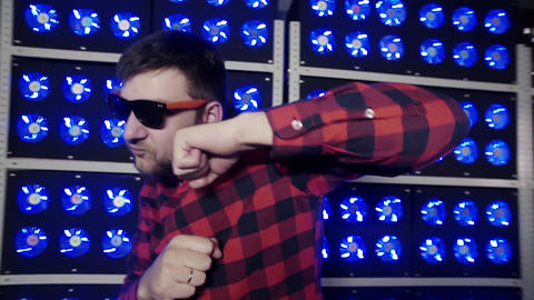 Guy with sunglasses shows boxing and dancing in room with illuminated coolers Footage