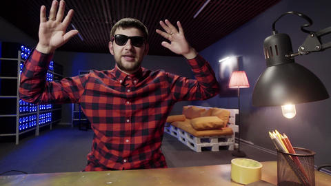 Charismatic male speaks, uses hand gestures looking at camera in furnished room Footage
