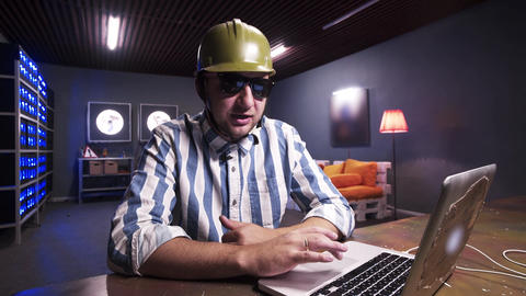 Attractive bearded guy put on sunglasses and green safety construction helmet Footage